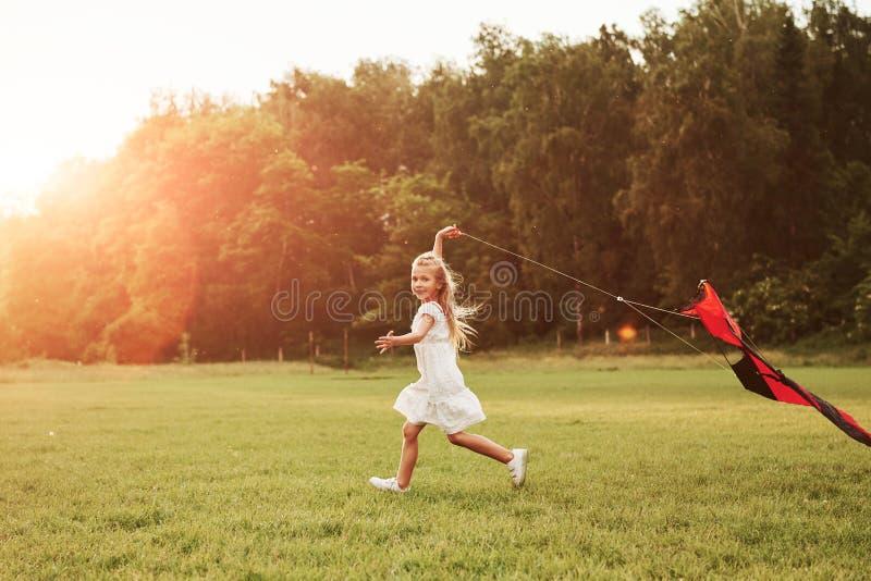 Kite está atrás da criança Garota feliz com roupas brancas se diverte no campo Bonita natureza foto de stock