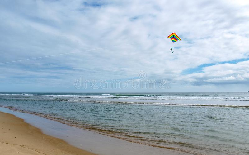 Kite Flying over Cape Hatteras National Seashore. A colorful kite flies above the waves at Cape Hatteras National Seashore in North Carolina royalty free stock images