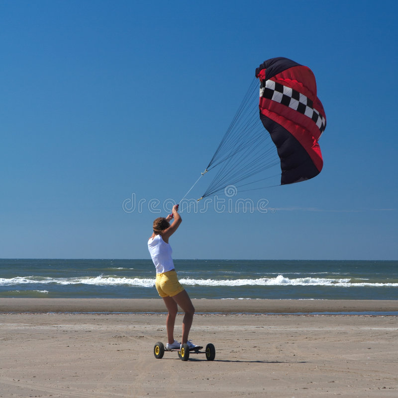 Kite girl. A young woman holding a kite on a skateboard on the beach racing. Red kite, yellow shorts, blue sky. The sea at the background with low tide royalty free stock image