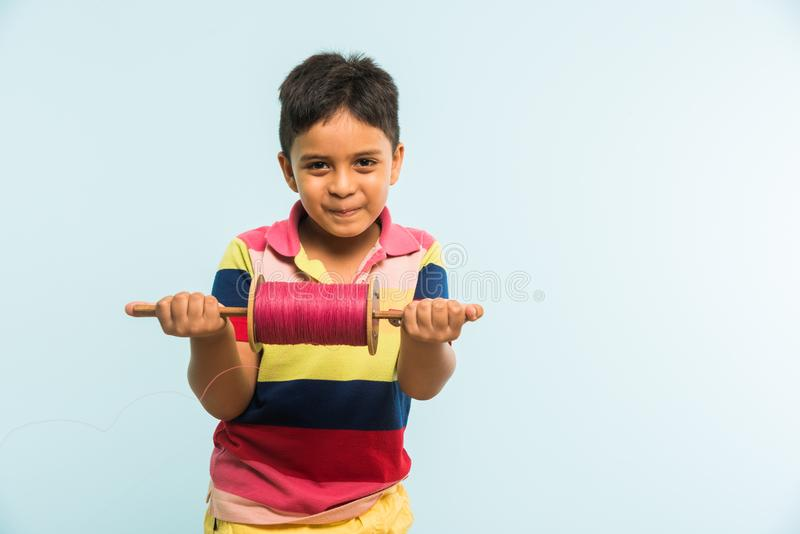Indian small kid or boy holding spindal or chakri on Makar Sankranti festival, ready to fly Kite. Kite or Patang flying in India, cute and happy little indian stock images