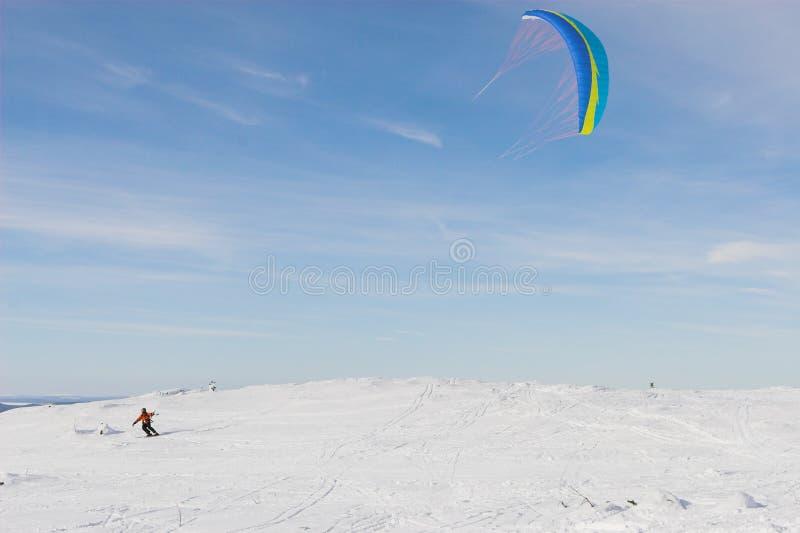 Kite-skiing. Mountain-skier with kite on the hill royalty free stock photo