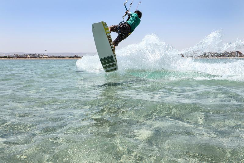Recreational water sports: kitesurfing. Kiteboarding sportsman jumping high in the sky on windy day. Extreme sports action royalty free stock photo