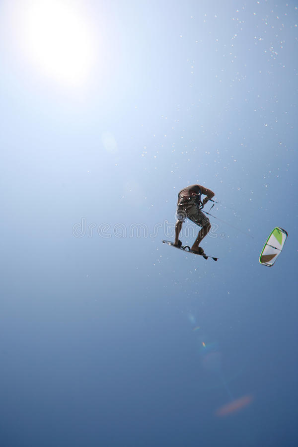 Kite surfer. Jumping towards the sun with water spray royalty free stock photos