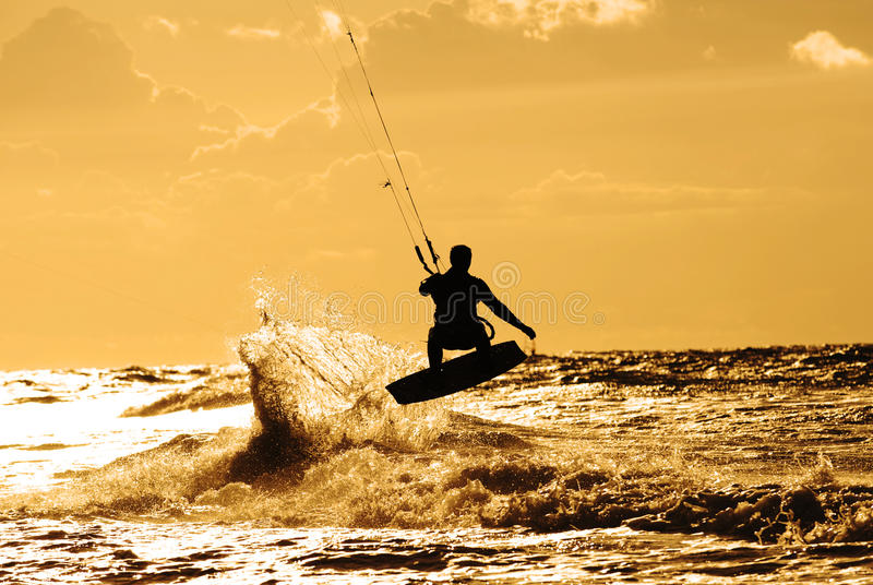 Kite surfer in action. Kite boarder in action, flying with his board over the splashing waves against the sunset royalty free stock photo