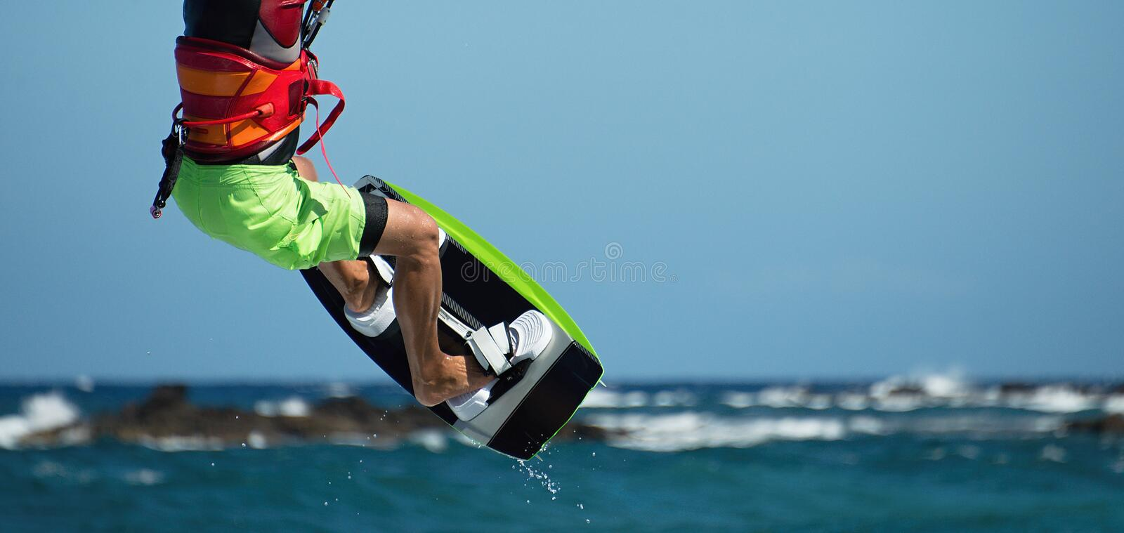Kite surfer flying over the wave stock photography