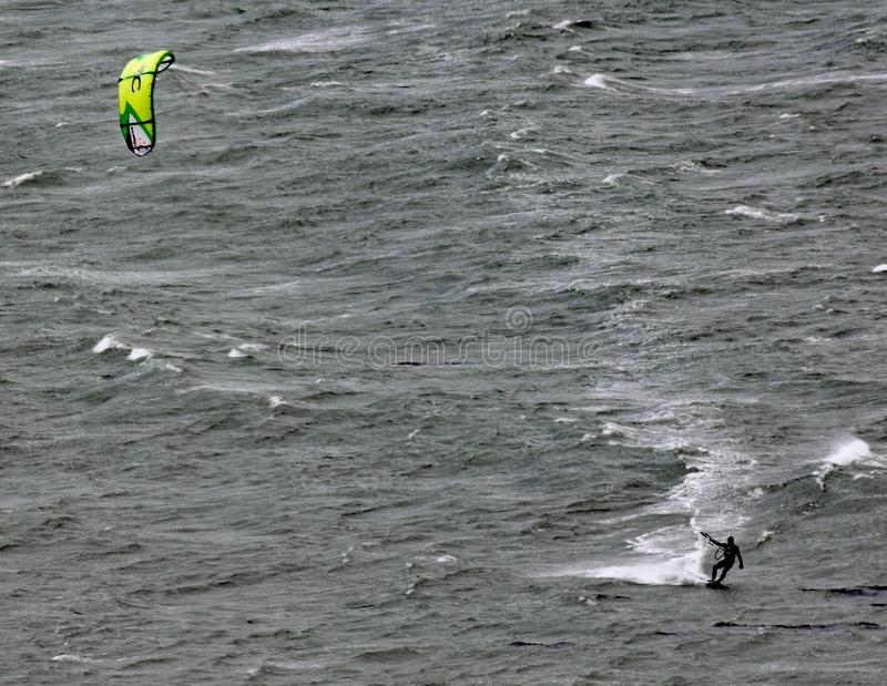 A kite surfer moves across Lyall Bay in Wellington New Zealand on a grey stormy day stock photography