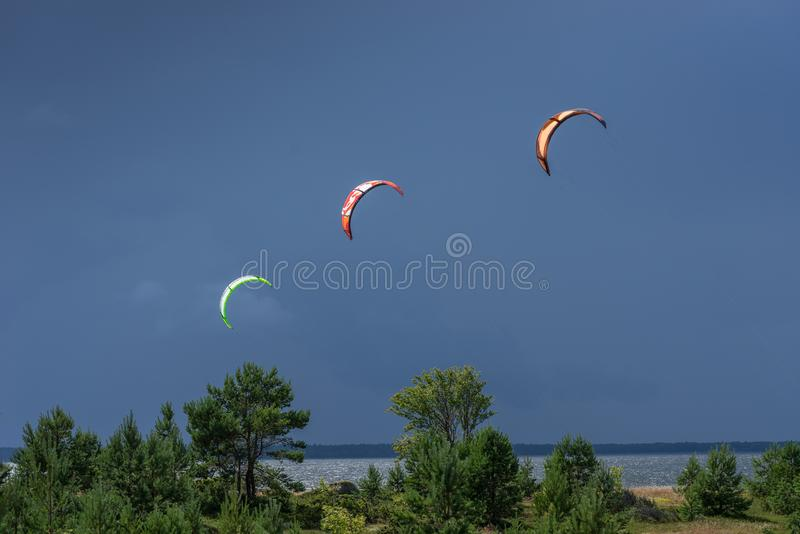 A kite surfer rides on the sea. Kites in the sky. stock image