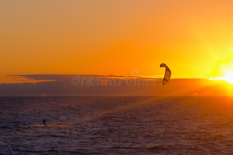 Kite surfer on sunset. Kite surfer surfing in ocean at sunset with sun royalty free stock images