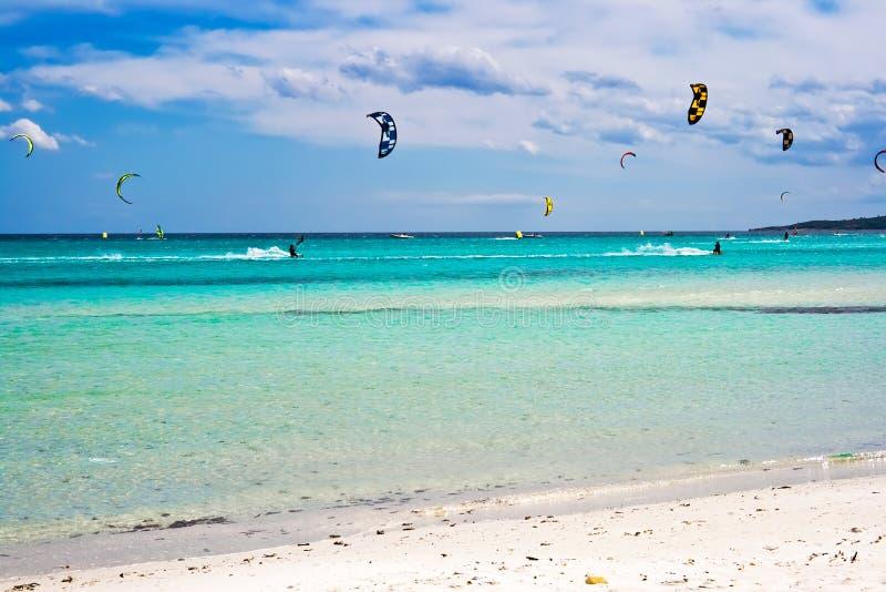 Kite surfers. Kitesurfers gliding at high speed around the beach la Cinta, Sardinia stock photography