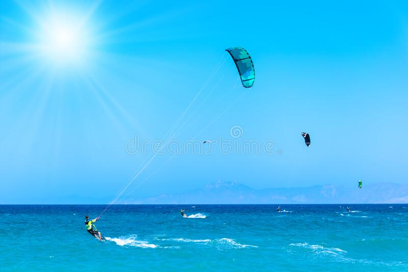 Kite surfers ride on waves on beach in Aegean Sea, blue sky and sunrays Rhodes, Greece royalty free stock images