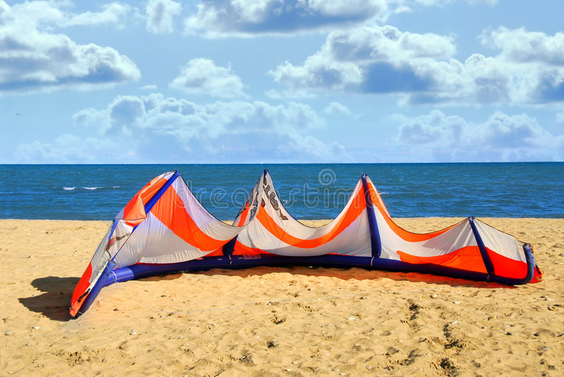 Kite surfing. Big kite for kite surfing lying on a sandy beach royalty free stock image