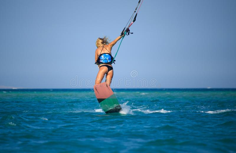 Kite surfing girl in sexy swimsuit with kite in sky on board in blue sea riding waves with water splash. Recreational activity,. Water sports, action, hobby and stock photos