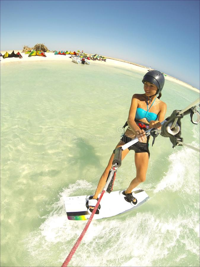 Kite surfing girl in sexy swimsuit with kite in sky on board in blue sea riding waves with water splash. Recreational activity,. Water sports, action, hobby and stock images