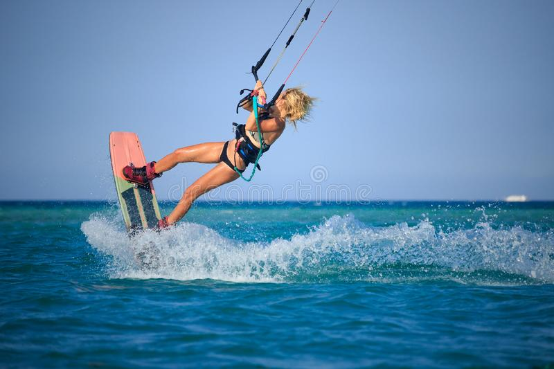 Kite surfing girl in sexy swimsuit with kite in sky on board in blue sea riding waves with water splash. Recreational activity. Water sports, action, hobby and stock images