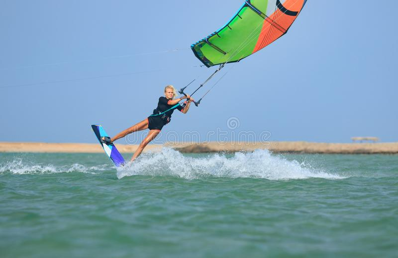 Kite surfing girl in sexy swimsuit with kite in sky on board in blue sea riding waves with water splash. Recreational activity. Water sports, action, hobby and stock image