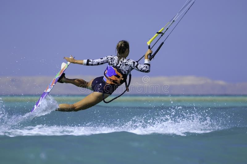 Kite surfing girl in sexy swimsuit with kite in sky on board in blue sea riding waves with water splash. Recreational activity. Water sports, action, hobby and royalty free stock photography