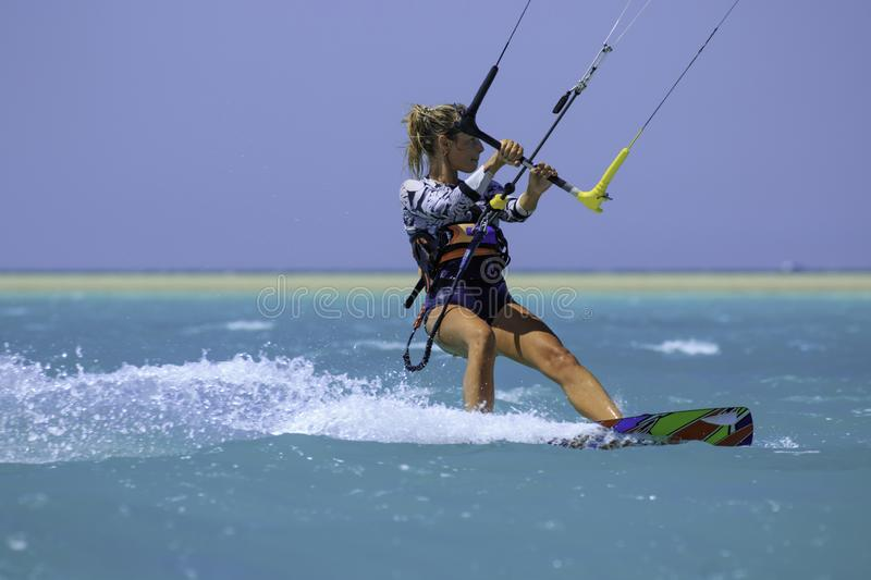 Kite surfing girl in sexy swimsuit with kite in sky on board in blue sea riding waves with water splash. Recreational activity. Water sports, action, hobby and royalty free stock image