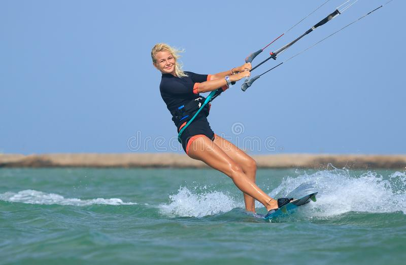 Kite surfing girl in sexy swimsuit with kite in sky on board in blue sea riding waves with water splash. Recreational activity,. Water sports, action, hobby and royalty free stock photography