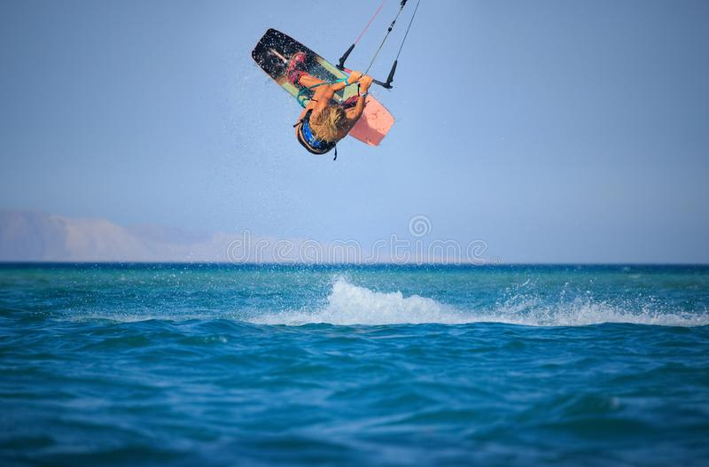 Kite surfing girl in sexy swimsuit with kite in sky on board in blue sea riding waves with water splash. Recreational activity,. Water sports, action, hobby and stock image