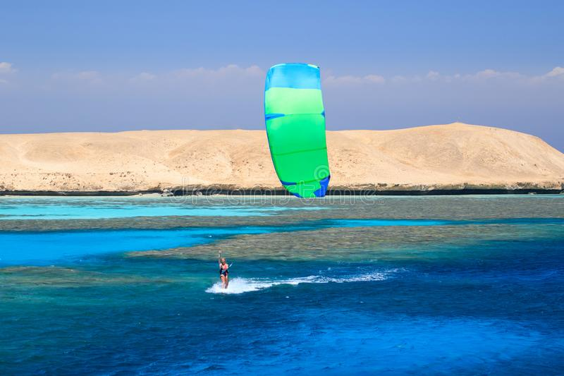 Kite surfing girl in swimsuit with kite in sky on board in blue sea riding waves with water splash. Recreational activity,. Water sports, action, hobby and fun stock photography