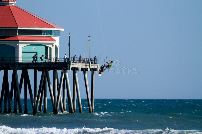 Kite Surfing At Huntington Beach Pier. Kite Surfing on a bright sunny day next to the Pier in Huntington Beach CA. The building is currently Ruby's Diner royalty free stock images