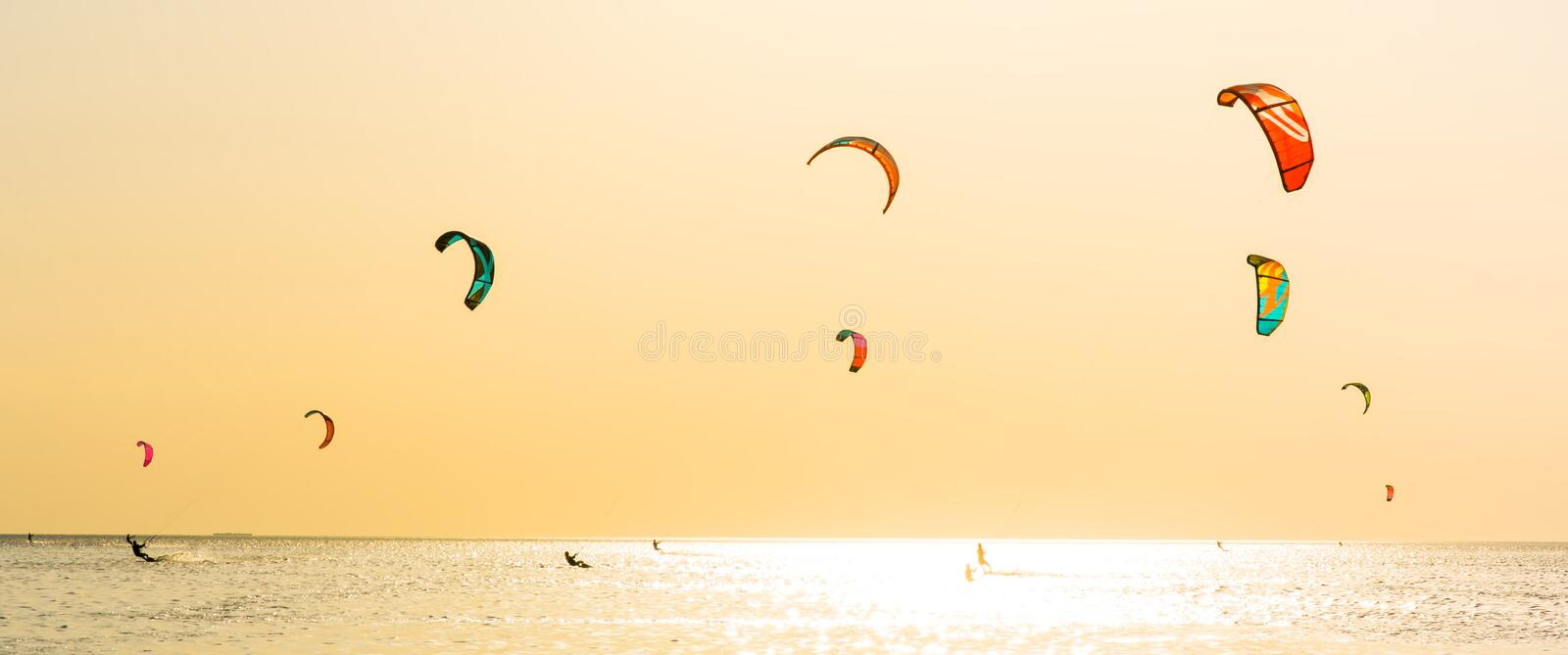 Kite-surfing and a lot of silhouettes of kites in the sky. Holidays on nature. Artistic picture. Beauty world. Panorama stock photos
