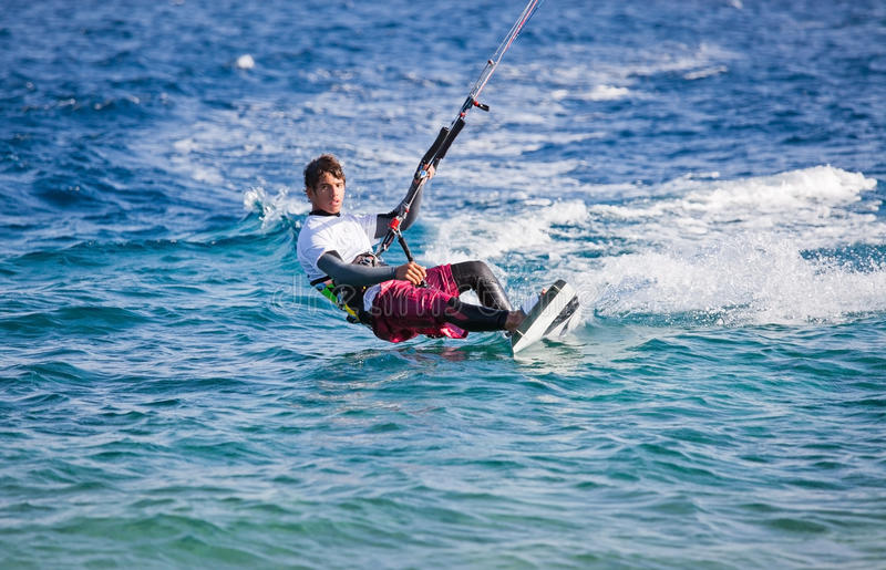 Kite surfing on the sea. The beautiful suntanned young guy goes for a drive on a board by the sea royalty free stock photo