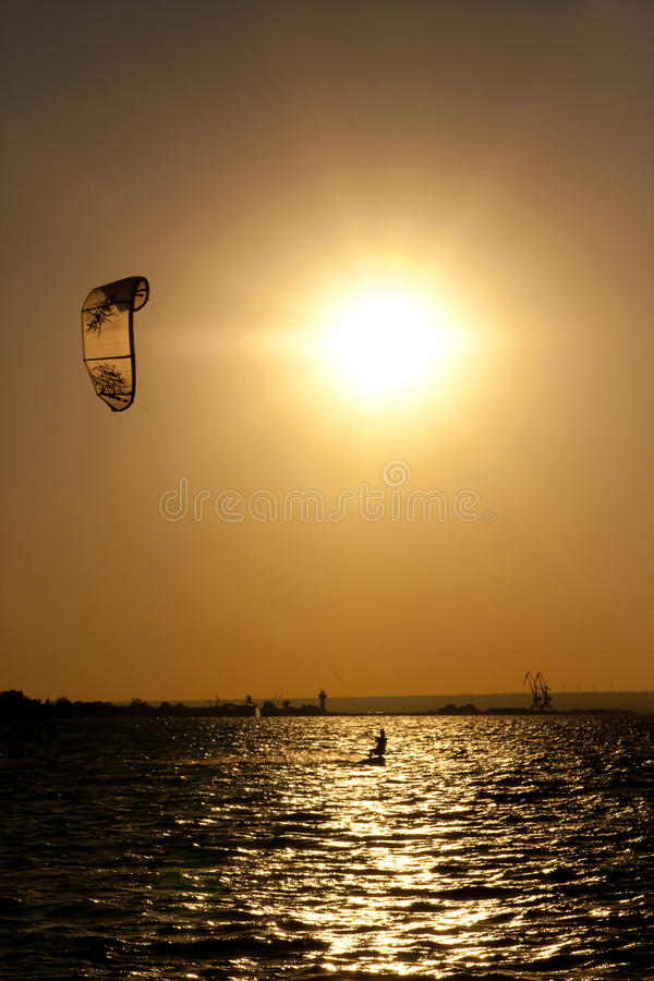 Kite-surfing and the sunset. Sepia-toned photo of the evening sun and the kite-surfer sliding on the water royalty free stock image