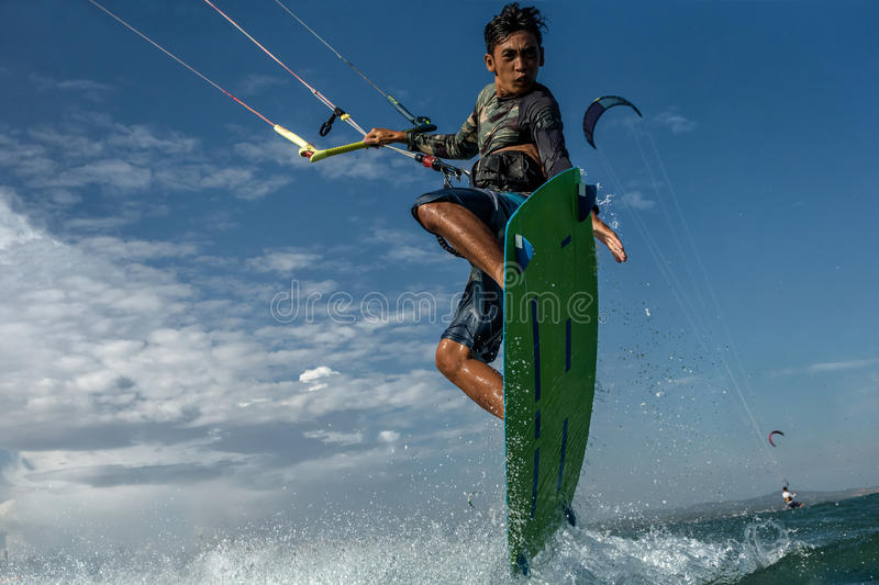 Kite surfing. A kite surfer rides the waves royalty free stock photos