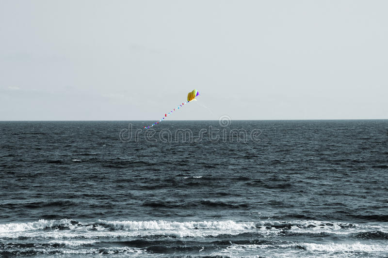 Kite in the Wind. The photograph of a flying kite in the wind. In the background is the sea royalty free stock images