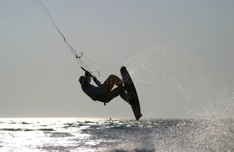 Kiteboarder, das für einen Sprung sich entfernt stockbild