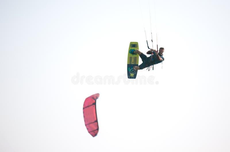 Kiteboarder idrottsman nen som utför kiteboarding kitesurfing trick arkivfoto