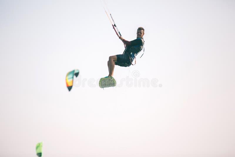 Kiteboarder idrottsman nen som utför kiteboarding kitesurfing trick royaltyfri fotografi