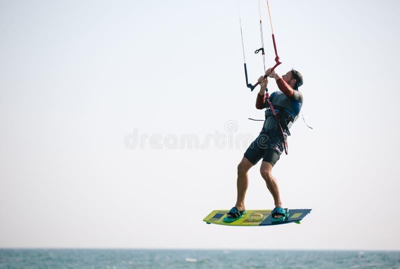 Kiteboarder idrottsman nen som utför kiteboarding kitesurfing trick arkivbild