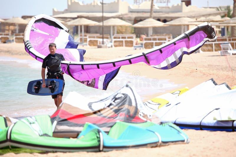 Kiteboarder with kite. Kiteboarder walking in the beach holding his kite stock photos