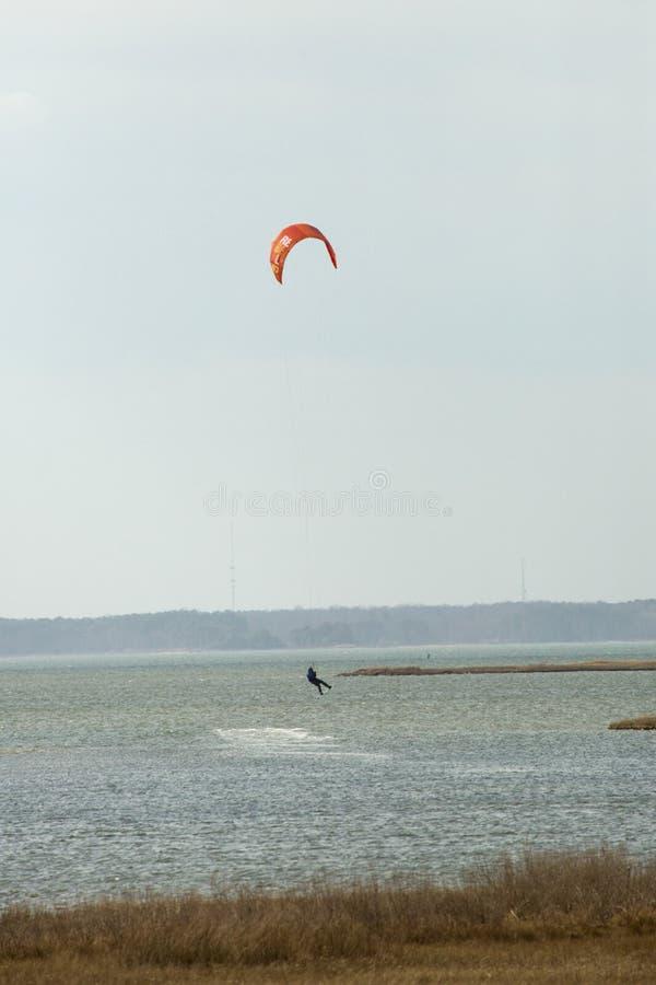 Kiteboarder pratica il surfing sulla baia di Sinepuxent fuori dall'isola di Assateague, Maryl immagine stock