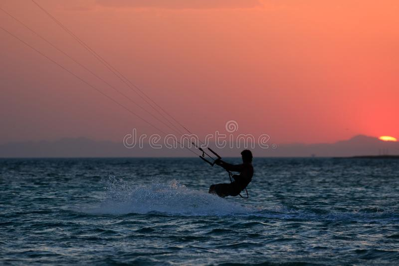 Kite boarder sportsman under sunset sun, freestyle kiteboarding rider on the evening kitesession, sunset in the sea, extreme royalty free stock photos