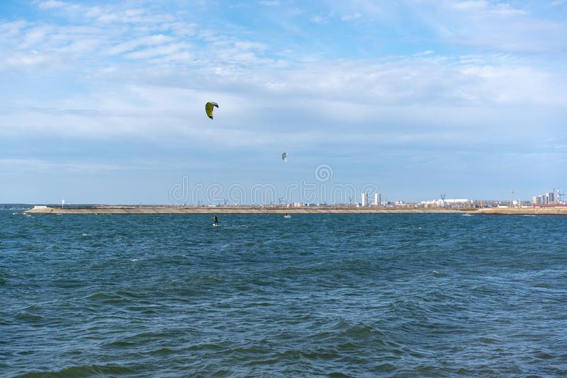 Kiteboarders ride on the sea stock images
