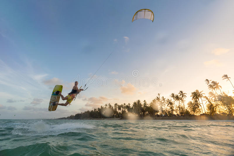 Kiteboarding. Fun in ocean. Extreme Sport Kitesurfing. Kiteboarding. Fun in the ocean. Extreme Sport Kitesurfing. Kitesurfer jumping high in the air during dusk stock photo
