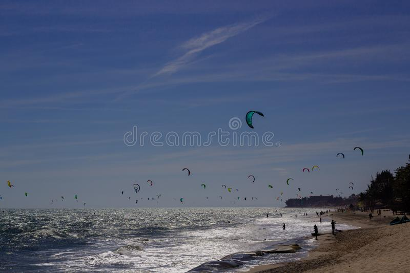 Kiteboarding, itesurfing at sunset in Mui Ne beach, Vietnam Phan Thiet.  stock photo