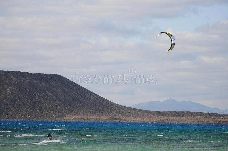Kiteboarding and Lobos island. Fuerteventura it is a great place for water sports royalty free stock photos