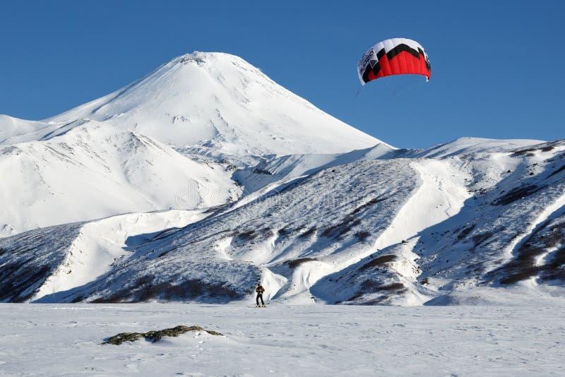 Kiteboarding - sportowiec sunie na nartach na tło wulkanie obraz stock