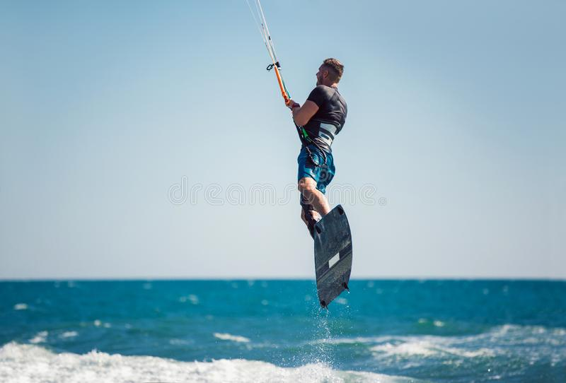 Kiter makes the difficult trick on a beautiful background. Kitesurfing Kiteboarding action photos man among waves. Professional kiter makes the difficult trick stock photos