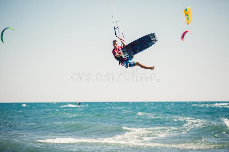 Kiter makes the difficult trick on a beautiful background. Kitesurfing Kiteboarding action photos man among waves. Professional kiter makes the difficult trick royalty free stock photography