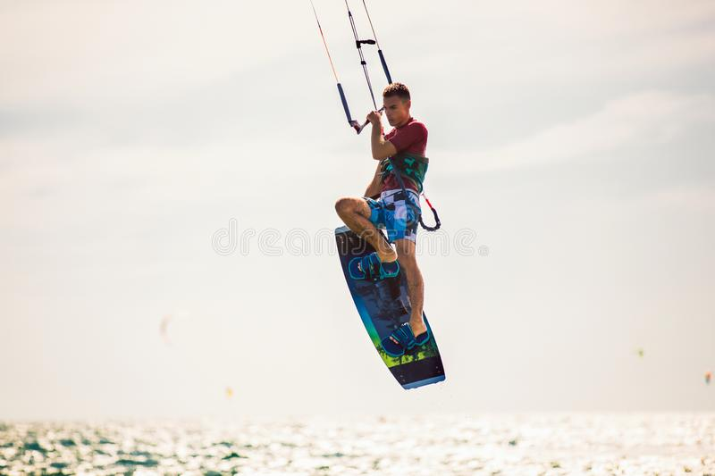 Kiter makes the difficult trick on a beautiful background. Kitesurfing Kiteboarding action photos man among waves stock photos