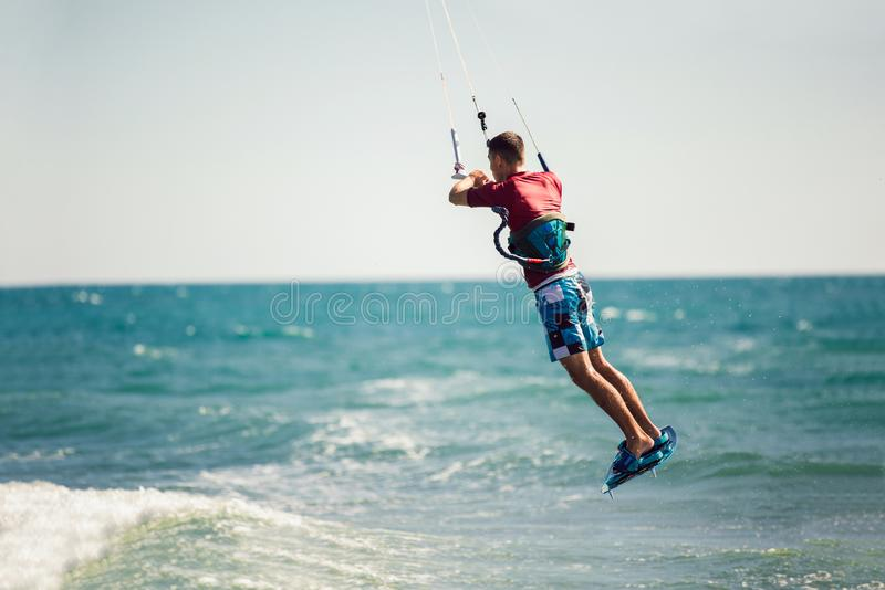 Kiter makes the difficult trick on a beautiful background. Kitesurfing Kiteboarding action photos man among waves. Professional kiter makes the difficult trick royalty free stock photo