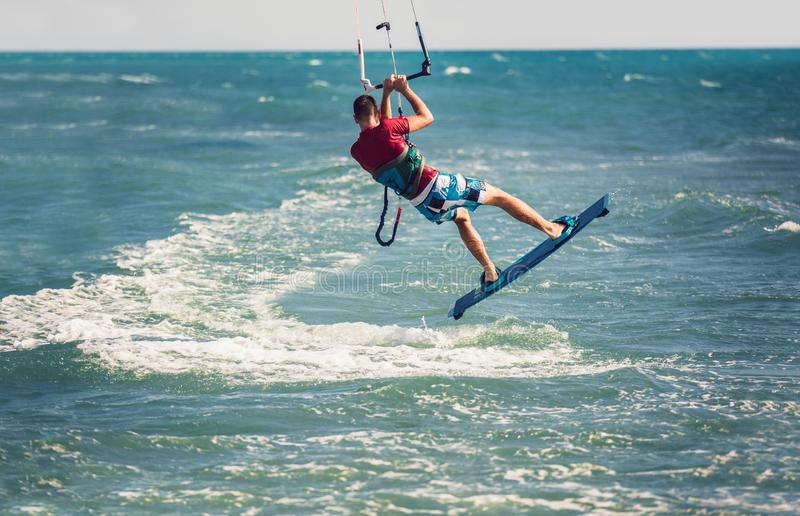 Kiter makes the difficult trick on a beautiful background. Kitesurfing Kiteboarding action photos man among waves stock images