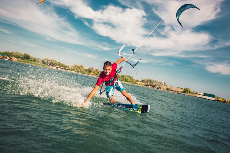 Kiter makes the difficult trick on a beautiful background. Kitesurfing Kiteboarding action photos man among waves royalty free stock photo
