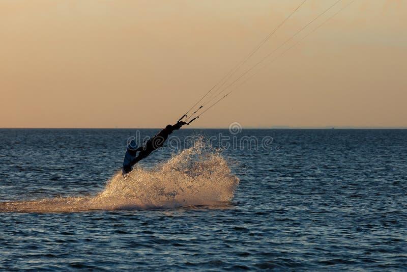 Kiter profesional que hace un truco complicado en un fondo hermoso de la puesta del sol foto de archivo