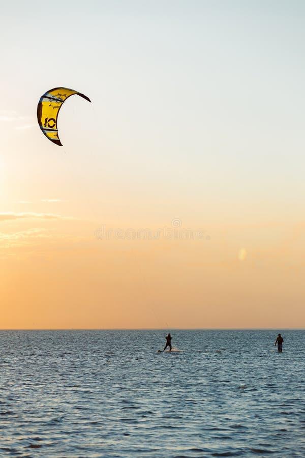 Kiter profesional que hace un truco complicado en un fondo hermoso de la puesta del sol fotos de archivo